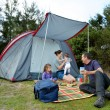 Family camping in a tent outdoors — Stock Photo #63217449