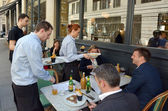 Waiters serving food and drinks to people dining in a restaurant — Stock Photo