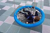 Happy little girl swings on Birds Nest Swing — Stock Photo