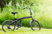 Black folding bicycle in grass — Stock Photo