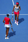 Grand Slam champions Serena Williams and Venus Williams during quarterfinal doubles match at US Open 2014 — Stock Photo