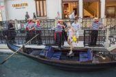 Gondeliers helpen toeristische aan boord van de gondel rit op Canal Grande in het Venetiaans Resort — Stockfoto