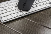 Notepad, keyboard, mouse and cellphone on wood table — Stock Photo