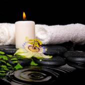 Spa setting of passiflora flower, green branch fern, towels and — Stock Photo