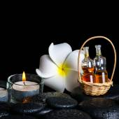 Aromatic spa setting of plumeria flower, candles and bottles ess — Stock Photo
