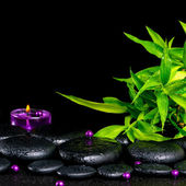 Beautiful spa concept of zen basalt stones with drops, lilac can — Stock Photo