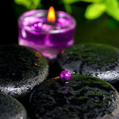 Spa concept of zen basalt stones with bead, drops, lilac candles — Stock Photo
