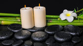 Spa concept of zen basalt stones, white flower plumeria, candles — Stock Photo