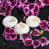 Beautiful spa still life of geranium flower and candles in rippl — Stock Photo