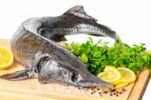 Fresh raw sturgeon fish with greens, lemon, different peppers an — Stock Photo