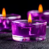 Three beautiful purple candles on a black background with water — Stock Photo