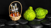 Aromatic spa concept of bottles essential oil in basket, bergamo — Stock Photo