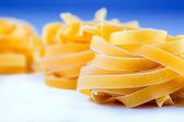 Tagliatelle pasta on white blue background.Macro concept — Stock Photo