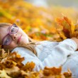 Young girl lying on the colored maple leaves in hands holding a bouquet from the same leaves — Stock Photo #55289603