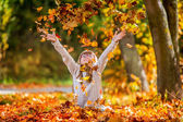 Sitting young girl playfully thrown away over his head colored maple leaves. — Stock Photo