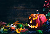 Jack o lanterns Halloween pumpkin face on wooden background and autumn leaves — Stock Photo