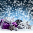 Purple Christmas package , gift of a silver ribbon. Jingle bells , silver christmas balls and christmas stars put on snow. Abstract multicolored blurred background space. — Stock Photo #58180319