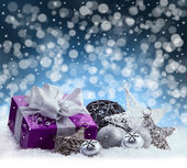 Purple Christmas package , gift of a silver ribbon. Jingle bells , silver christmas balls and christmas stars put on snow. Abstract multicolored blurred background space. — Stock Photo