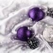 Luxury Christmas balls Silver pine cones on white satin Christmas decoration combined purple and silver colors. Glittering background of bright stars and snowflakes. Frozen Frame — Stock Photo #59767717