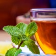 Tea in a glass bottle, mint leaves, dried tea, sliced lime, cane sugar — Stock Photo #65153785