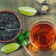 Tea in a glass bottle, mint leaves, dried tea, sliced lime, cane sugar — Stock Photo #65153867