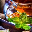 Tea in a glass bottle, mint leaves, dried tea, sliced lime, cane sugar — Stock Photo #65153883