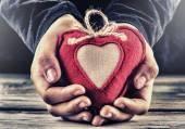 Red canvas valentine heart in the hands of a child. Heart gift as a token of love. — Stock Photo