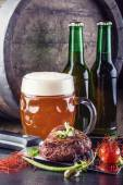Beef steak withvegetable decoration. Beer barrel with beer glass and bottle — Stock Photo