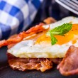 Ham and Egg. Bacon and Egg. Salted egg and sprinkled with black pepper and green herb decoration. — Stock Photo #71774361