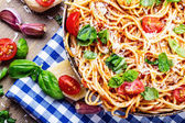 Spaghetti bolognese with cherry tomato and basil. Spaghetti with tomato sauce on blue checkered tablecloth and rustic wooden table — Stock Photo