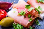 Curled Slices of Delicious Prosciutto with parsley leaves on granite board. — Stock Photo