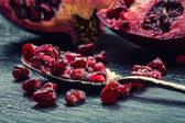 Pieces and grains of ripe pomegranate. Pomegranate seeds. Part of pomegranate fruit on granite board and antique spoon. — Stock Photo
