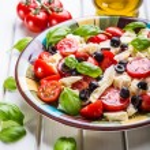 Постер, плакат: Caprese Caprese salad Italian salad Mediterranean salad Italian cuisine Mediterranean cuisine Tomato mozzarella basil leaves black olives and olive oil on wooden table