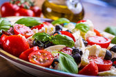 Caprese. Caprese salad. Italian salad. Mediterranean salad. Italian cuisine. Mediterranean cuisine. Tomato mozzarella basil leaves black olives and olive oil on wooden table. — Stock Photo