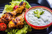 Tzatziki sauce. Tzatziki dressing. Tzatziki dressing with grilled chicken legs and fresh vegetable,lettuce leaf and cherry tomatoes. Grilled chicken legs, lettuce and tomatoes. — Stock Photo