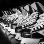 Постер, плакат: Hockey skates lined up in locker room