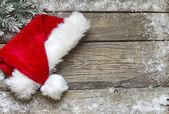 Santa Claus hat on vintage wooden boards christmas background — Stok fotoğraf
