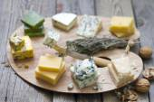 Various types of cheese on abstract vintage paint palette — Stock Photo