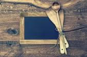 Kitchen utensils and vintage blackboard on wooden background — Stock Photo