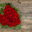Heart shaped red roses bouquet on rustic wooden background — Stock Photo #54042609