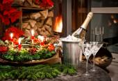 Christmas decoration. bottle of champagne, glasses and fireplace — Stock Photo