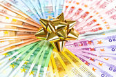 Money as a gift. golden ribbon on euro banknotes background — Stock Photo