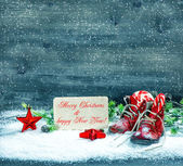 Christmas decoration red stars and antique baby shoes in snow — Stock Photo