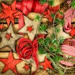 Christmas ornaments, wooden stars, red ribbons and pine tree bra — Stock Photo #57295547