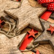 Christmas ornaments wooden stars and red ribbons — Stock Photo #57296035