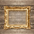 Antique golden frame over rustic wooden background — Stock Photo #58878323