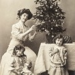 Happy mother and children with christmas tree and antique toys — Stock Photo #58916835