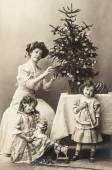 Happy mother and children with christmas tree and antique toys — Foto de Stock