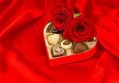 Красные розы и шоколадные пралине в подарочной коробке в форме сердца — Стоковое фото