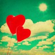 Blue sky with white clouds and red heart shaped balloons — Stock Photo #62873635